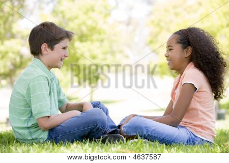 Tow Young Friends Sitting Outdoors Looking At Each Other And Smiling