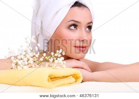 Beautiful young woman with flowers and towel on her head isolated on white