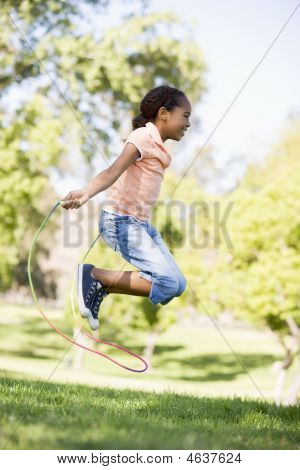 Young Girl Using Skipping Rope Outdoors Smiling