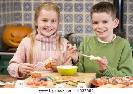 Brother And Sister At Halloween Making Treats And Smiling