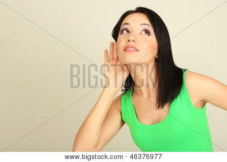 Girl overhears on grey background