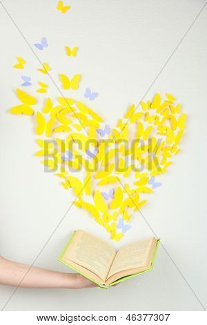 Paper yellow butterfly in form of heart fly out book