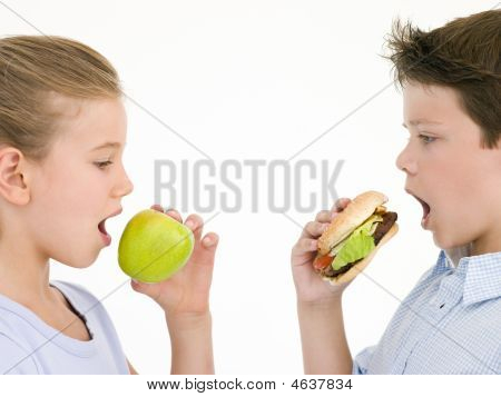 Sister Eating Apple By Brother Eating Cheeseburger