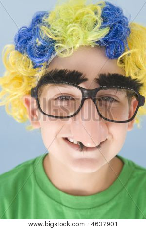 Young Boy Wearing Clown Wig And Fake Nose Smiling