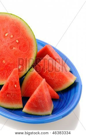 Closeup of a seedless watermelon on a blue platter. Half a melon surrounded by wedges of fruit. Vertical format on a white background with reflection.