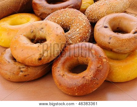 Closeup of a group of assorted bagels on a wood table top with burlap in the background. Bagels include, egg, whole grain, cinnamon raisin, sesame seed