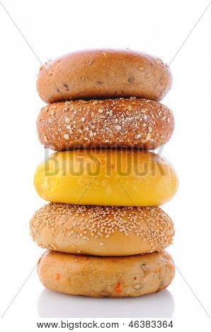 A stack of five different bagels on a white background with reflection. Bagels include: sesame seed, cinnamon raisin, multi grain, egg, and everything.