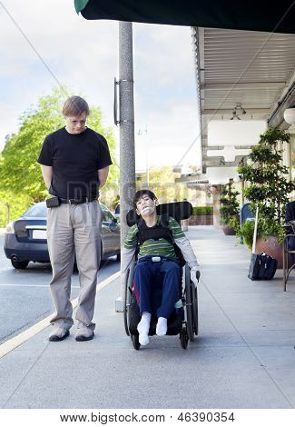 Father Walking Next To Disabled Son In Wheelchair Through Town