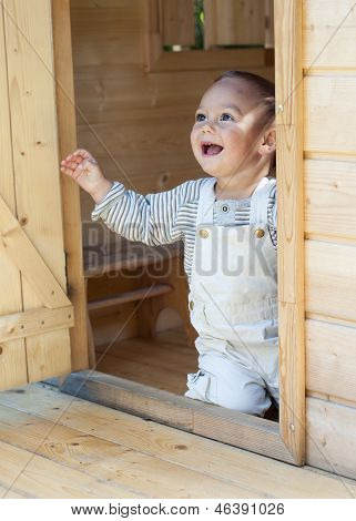Child in wooden shed playhouse.
