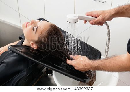 Hands of hairstylist washing client's hair at beauty parlor