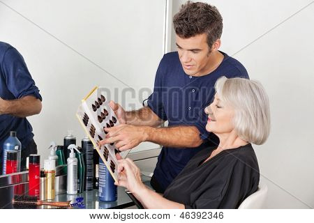 Hairstylist with catalog choosing hair color for female customer at parlor
