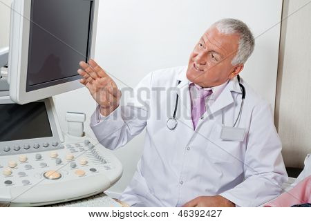 Senior male radiologist showing something on ultrasound machine's screen