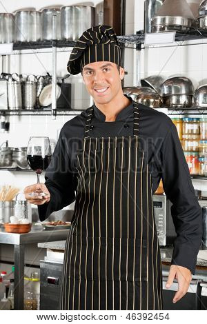 Portrait of young male chef holding glass of red wine at commercial kitchen