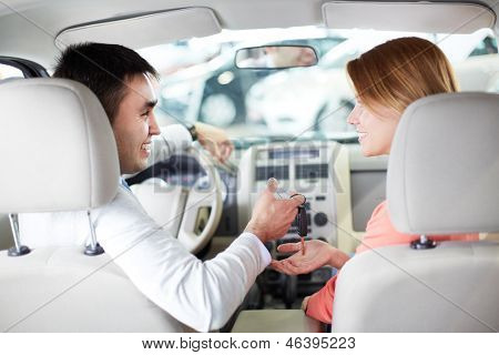 Rear view of pretty woman looking at salesman while taking key from new car