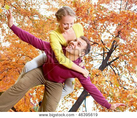 Happy couple on background of autumn leaves