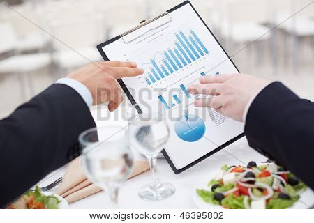 Close-up of business document and male hands pointing at it during business lunch