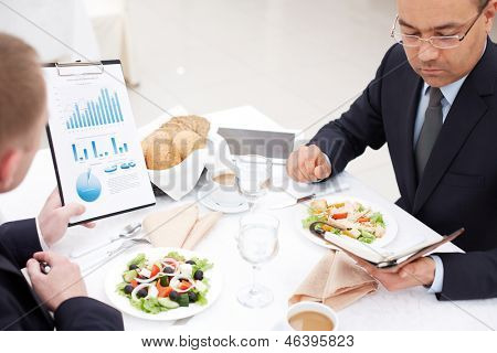 Confident businessmen planning work at business lunch