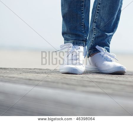 Woman Standing Outdoors In Blue Jeans And Comfortable White Shoes