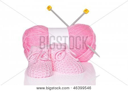 Baby girl knitted booties with pink wool and knitting needles, isolated on a white background.