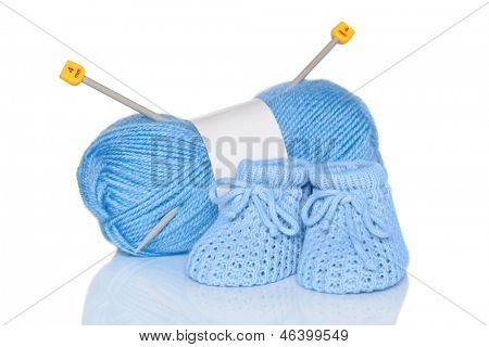 Baby boy knitted booties with blue wool and knitting needles, isolated on a white background.