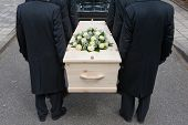 stock photo of mortuary  - Bearers a carrying a coffin into a car - JPG