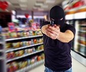 stock photo of derringer pistol  - Man in a mask with a gun in the supermarket - JPG