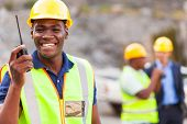 picture of ppe  - cheerful afro american mine worker with walkie talkie - JPG