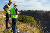 stock photo of ppe  - two male surveyors working at mining site - JPG