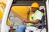 foto of heavy equipment operator  - african industrial worker operating bulldozer while talking on walkie - JPG
