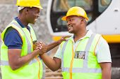 stock photo of ppe  - cheerful african mine workers hands together to form brotherhood - JPG