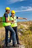 stock photo of ppe  - two male surveyors at work - JPG