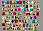 picture of glyphs  - Letters and numbers cut out from old magazines and newspapers Isolated on gray background - JPG