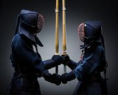Two kendo fighters with shinai opposite each other. Japanese martial art of sword fighting