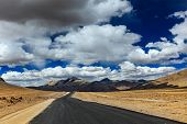 Travel forward concept background - road on plains in Himalayas with mountains and dramatic clouds.
