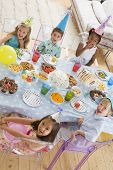 image of tea party  - Young children at party sitting at table with food smiling - JPG