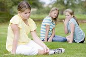 stock photo of obese children  - Two young girls bullying other young girl outdoors - JPG