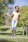 picture of jump rope  - Young girl using skipping rope outdoors smiling - JPG