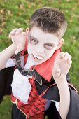 stock photo of fancy-dress  - Young boy looking into camera outdoors wearing vampire costume on Halloween - JPG