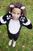 stock photo of fancy-dress  - Young girl outdoors looking into camera in cat costume on Halloween - JPG