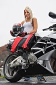 stock photo of crotch-rocket  - A pretty blonde posing with her motorcycle and riding gear - JPG