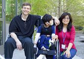 stock photo of biracial  - Disabled biracial six year old boy in wheelchair with parents outdoors