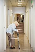 stock photo of zimmer frame  - Full length of a tired elderly woman with walker standing in hospital passageway - JPG