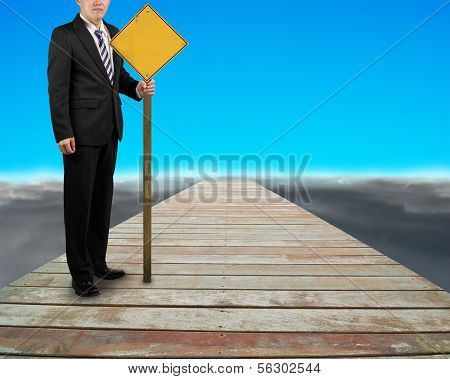 Businessman Hold Yellow Board Standing On Wooden Way