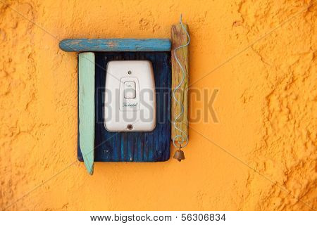 The doorbell button with wooden decoration on the old yellow wall.