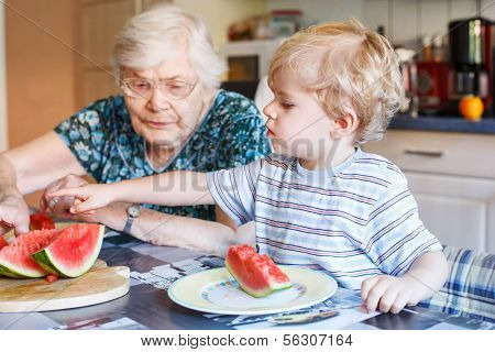 Little Toddler Boy And His Great Grandmother Eating Watermelon At Home