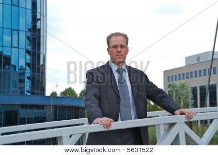 Businessman Standing On A Bridge
