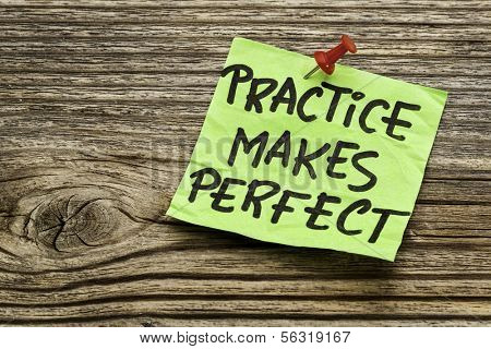 practice makes perfect - a motivational reminder on a green stocky note against grained wood