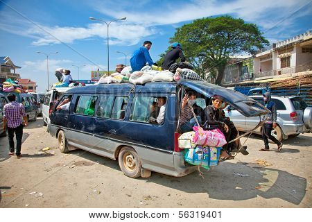 NEAK LEUNG, CAMBODIA - NOV 19, 2013: Passengers sit atop a very overloaded vehicle in Neak Leung on Noveber 17, 2013, Cambodia. This kind of domestic transportation carries between 16 to 30 passengers.