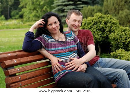 Young Happy Couple (pregnant Woman) On Bench