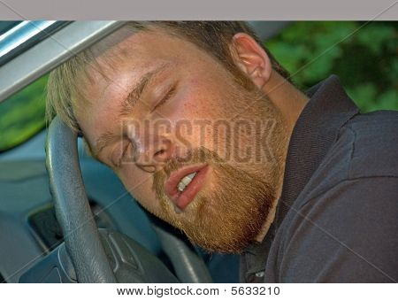 Man Asleep In A Car At The Wheel